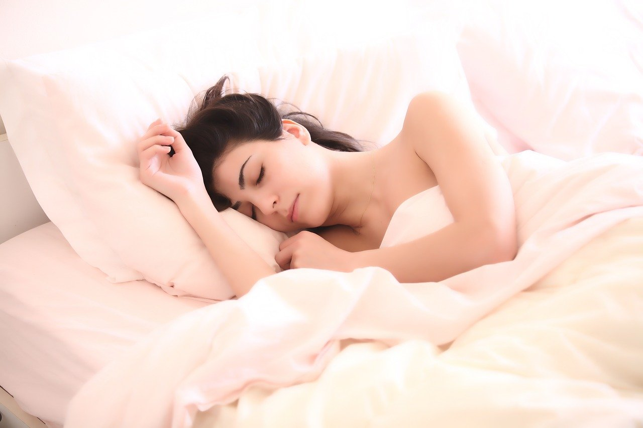A woman sleeping on a white bed