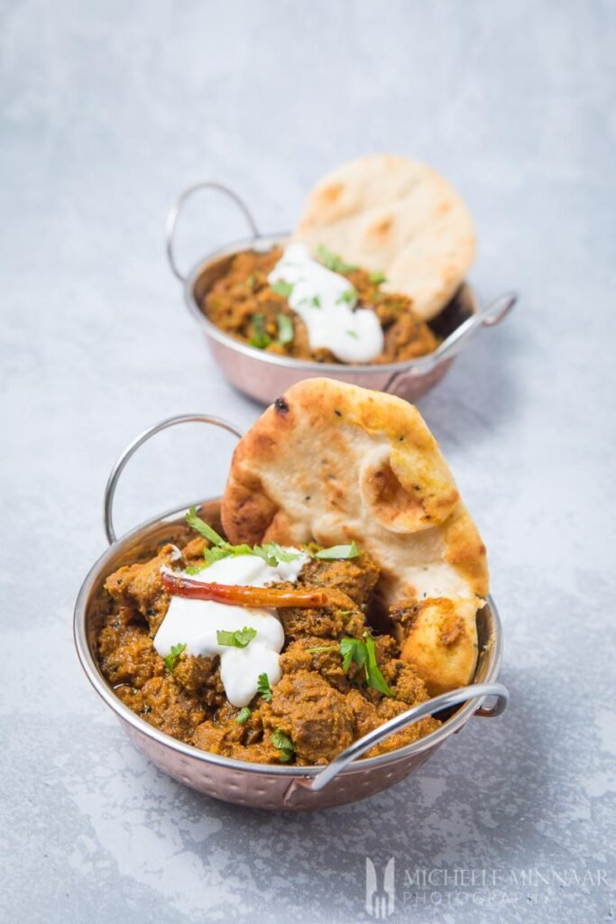 achar gosht in silver bowls with naan next to it
