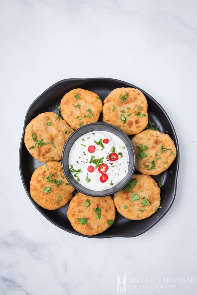 A platter of round aloo ki kachori with a bowl of yogurt