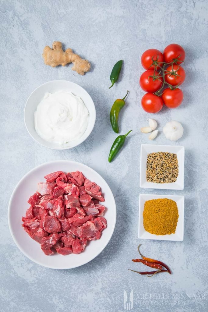 Ingredients to make achar gosht : tomatoes, beef, spices, peppers, ginger