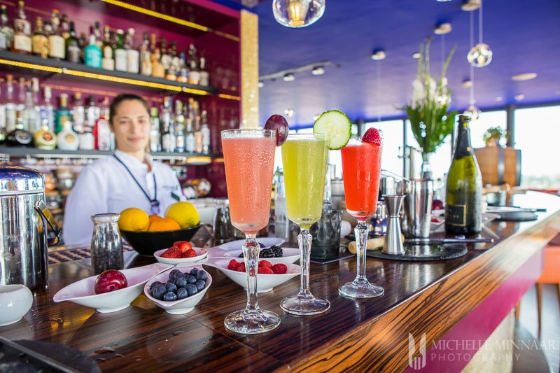 Three colorful cocktails on a bar