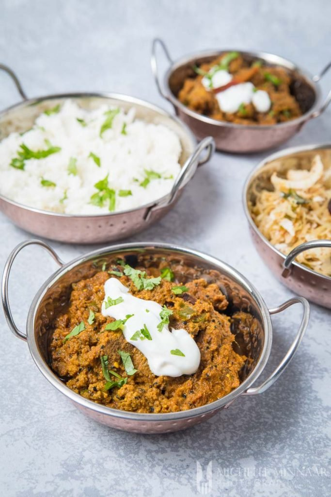A close up of achar gosht, shredded beef with sour cream on top