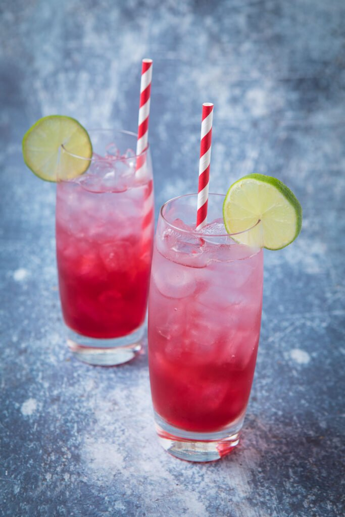 Two glasses of red and clear long beach iced tea with lime wheels as garnish and a red and white straw