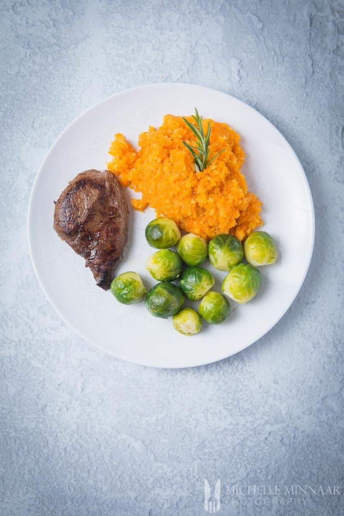 A plate with venison, brussel sprouts and orange mash