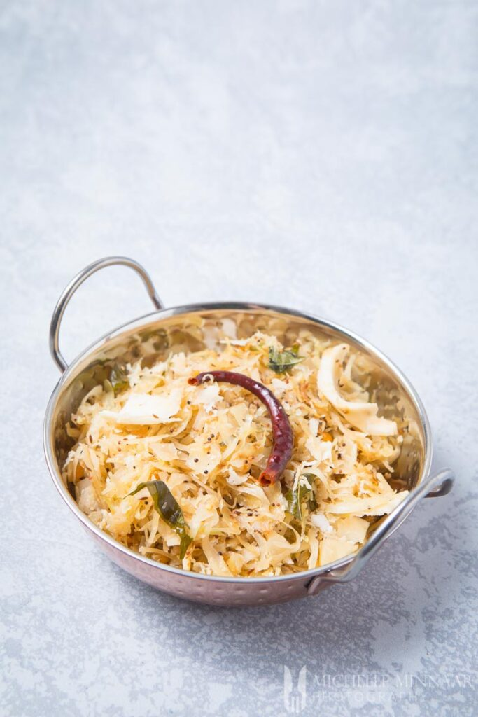 A bowl of white shredded cabbage poriyal