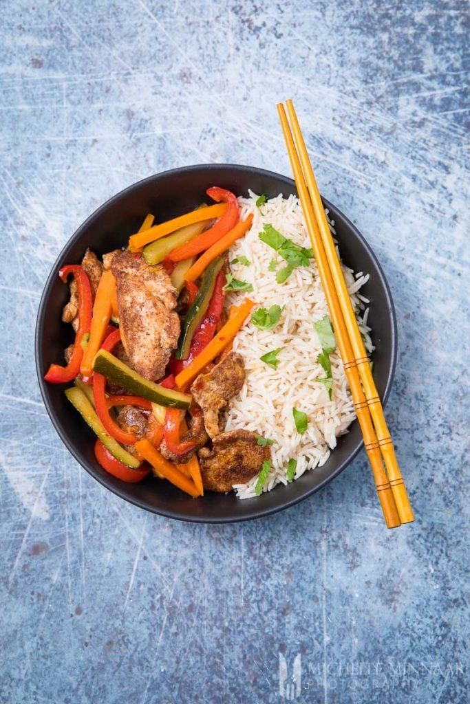 A bowl of sweet chili chicken stir fry and rice with chopsticks
