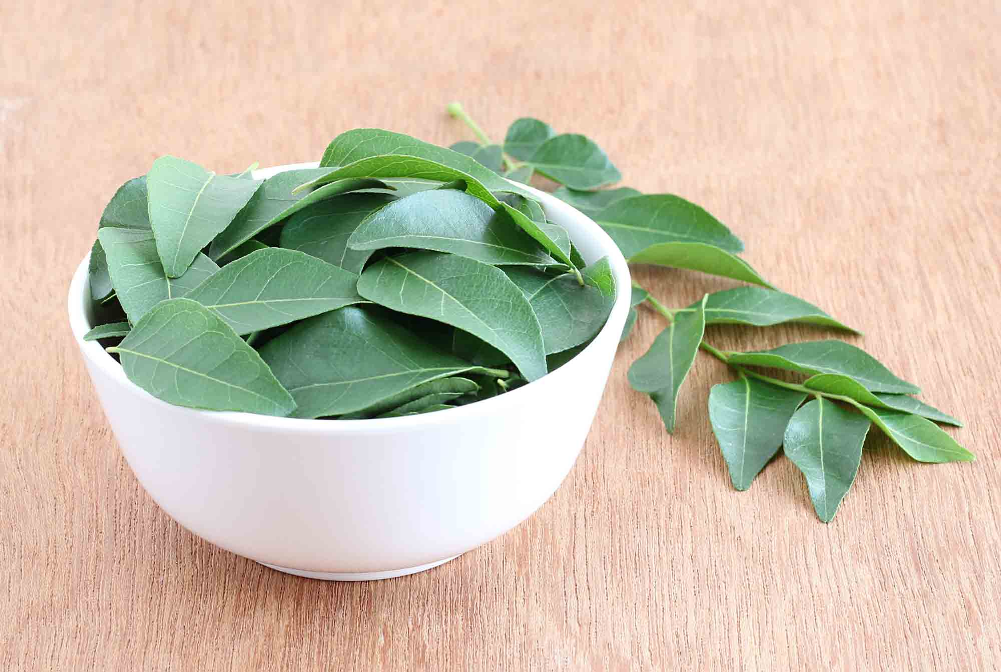 Green curry leaves in a bowl