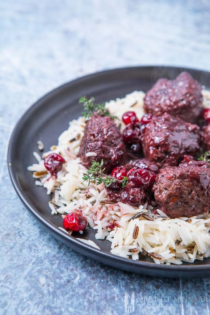 A finished plate of venison meatballs covered in a cranberry sauce over rice