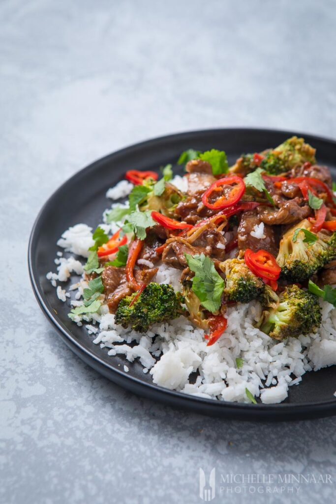 A plate of lamb stir fry over white rice