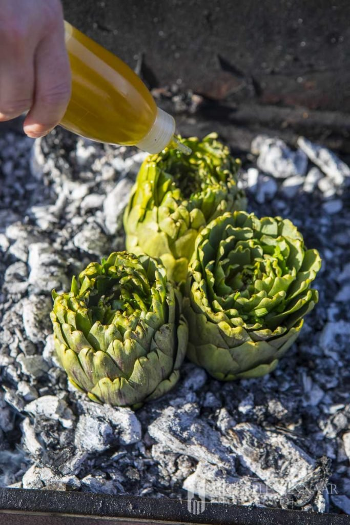 Oil being drizzled showing you how to cook artichokes