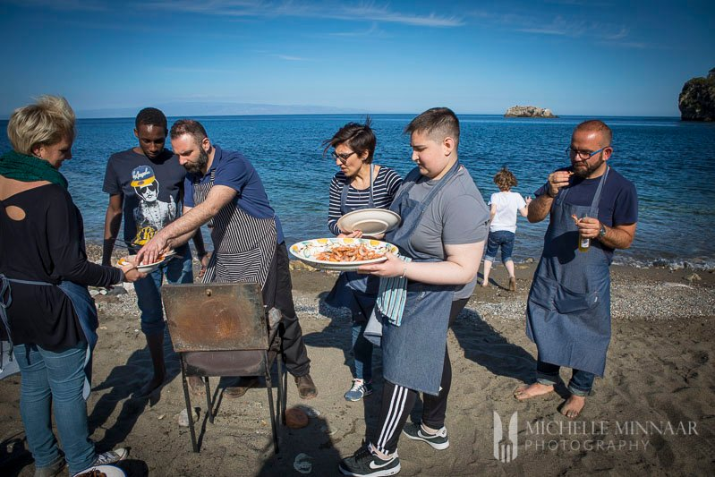 A group of people on a beach getting food