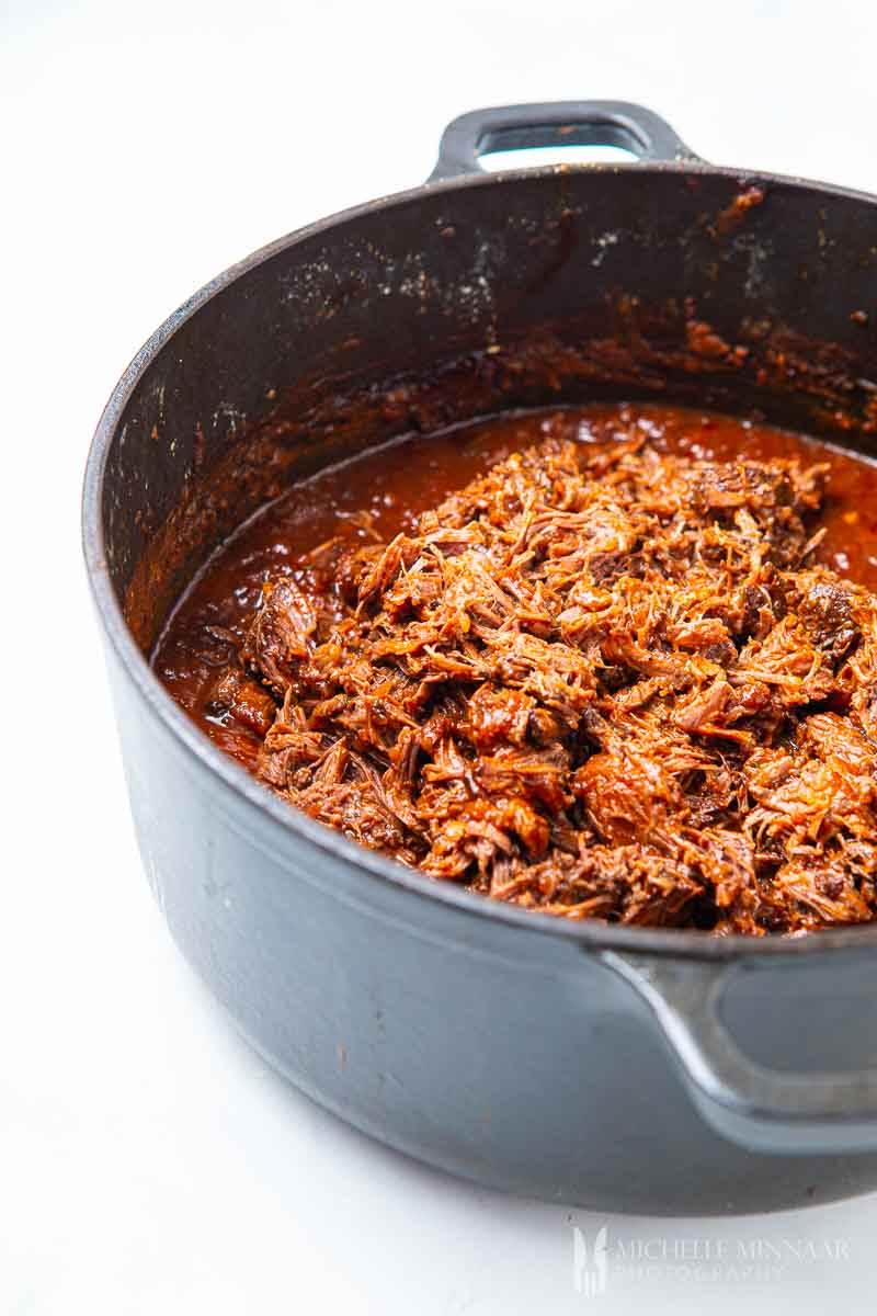 shredded beef in a pot simmering
