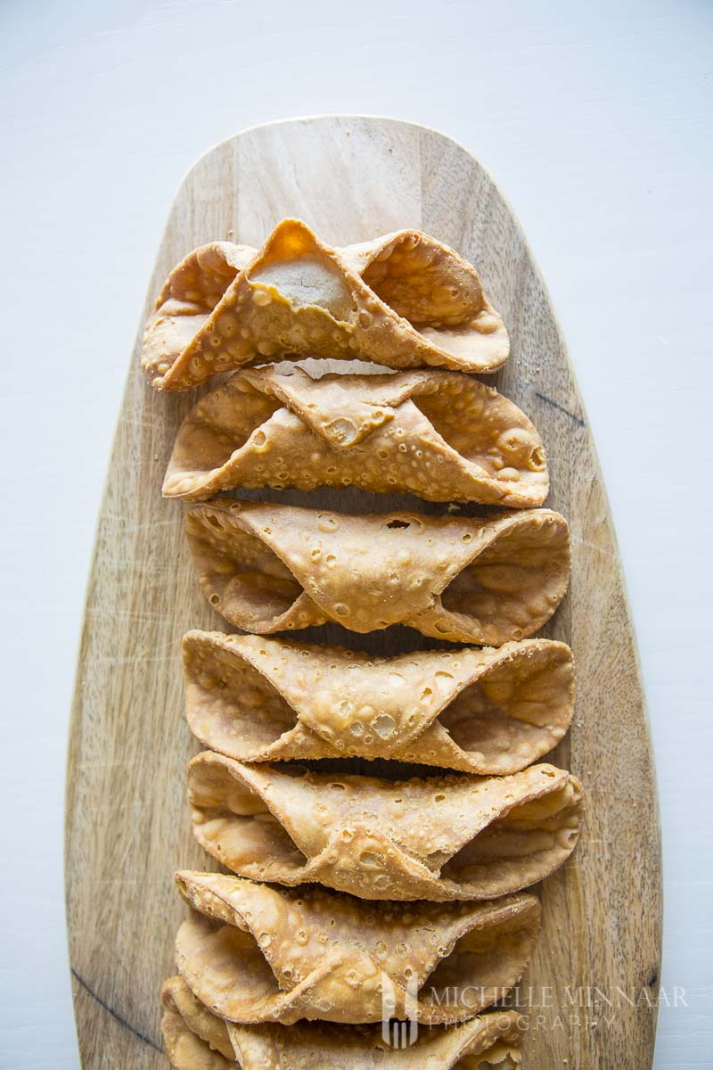 Empty brown cannoli Shells on a cutting board