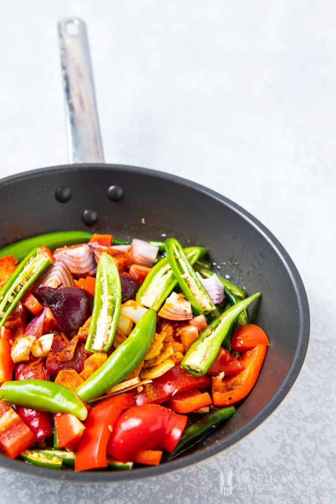 A close up of vegetables cooking in a saute pan