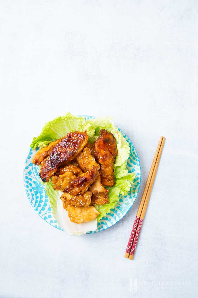 A plate of marmite chicken with a brown sauce on a bed of lettuce,