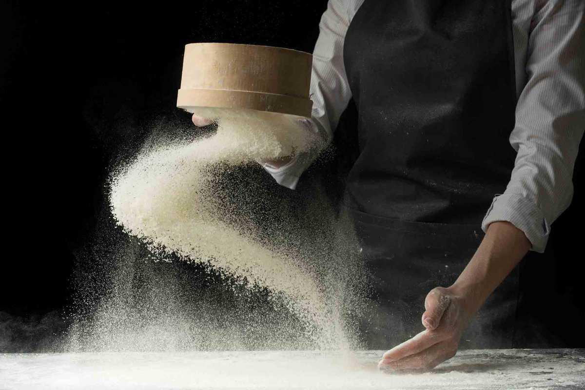 A man throwing masa harina flour