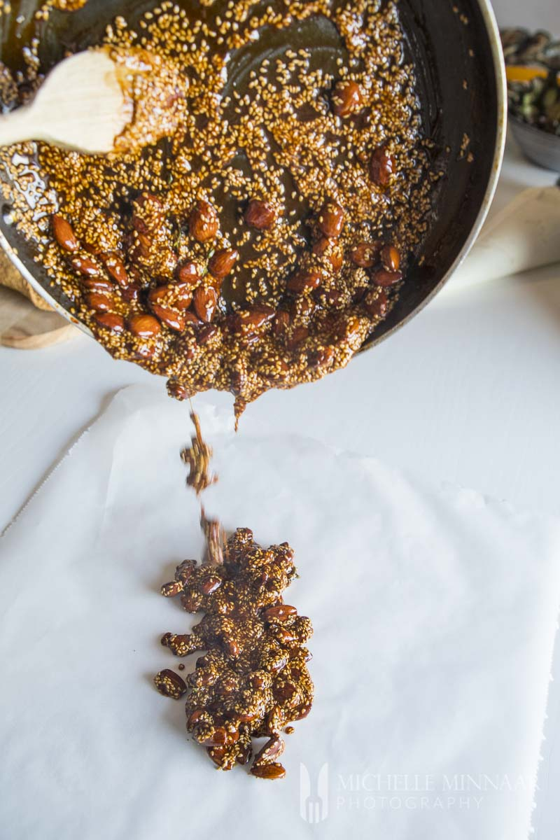 almond brittle being poured out onto a counter