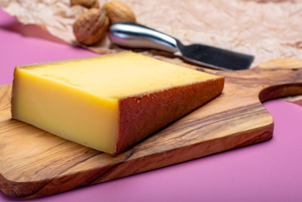 A slicce of yellow gruyere cheese