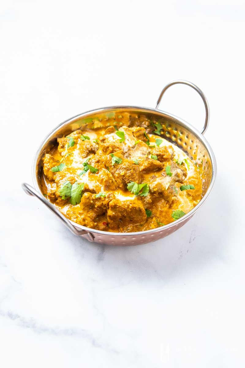 A bowl of beef korma, beef and brown curry sauce in a silver bowl