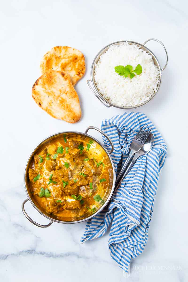 A bowl of beef korma, naan bread and white rice