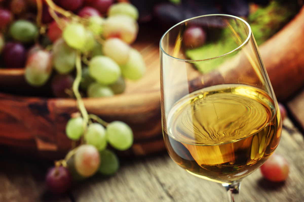 One light yellow glass of ice wine in a glass and grapes