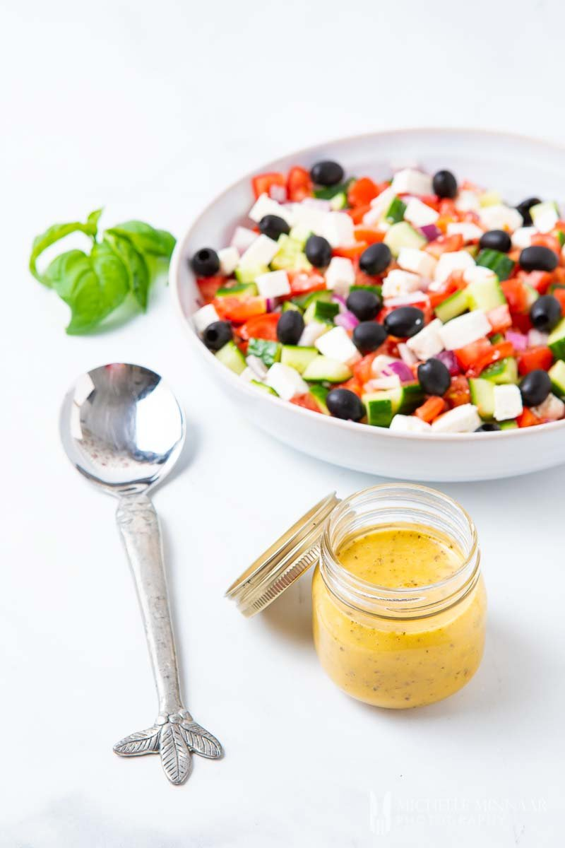 A greek salad with a jar of Mediterranean Salad Dressing