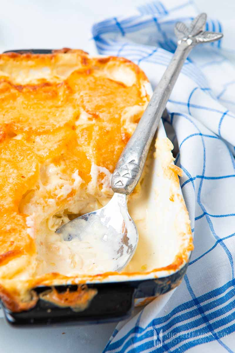 Close up of a spoonful of cheesy gratin dauphinois