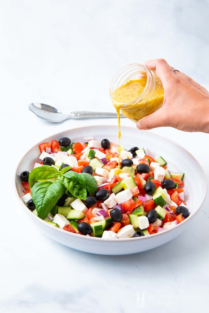Mediterranean Salad Dressing being poured onto a colorful greek salad