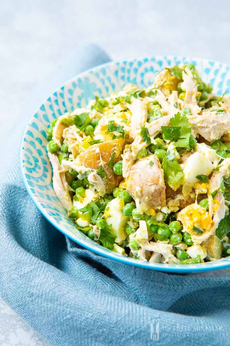 A close up of potatoes, chicken and peas