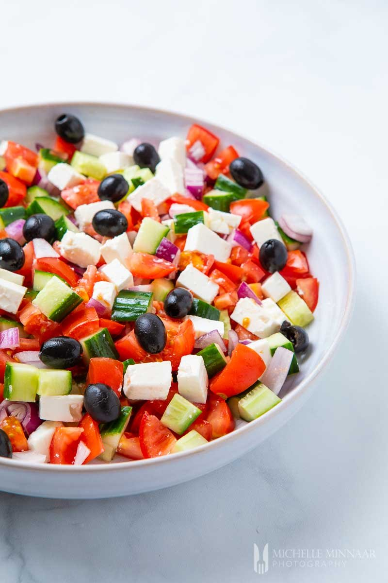 A close up of tomatoes, black olives, feta cheese and peppers