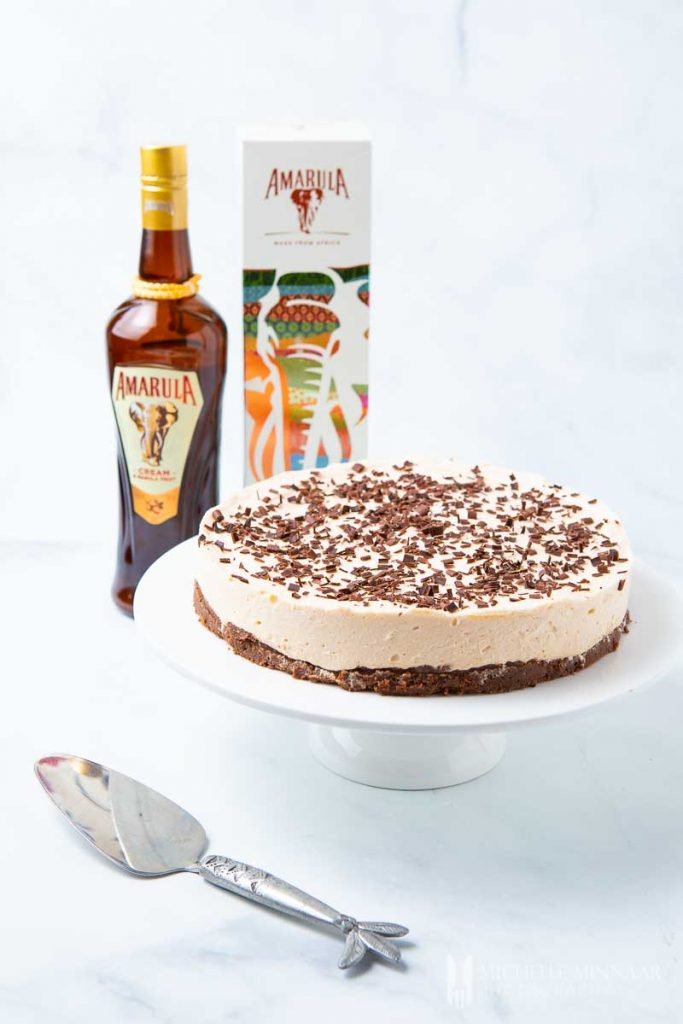 A cheesecake and a bottle of liquor