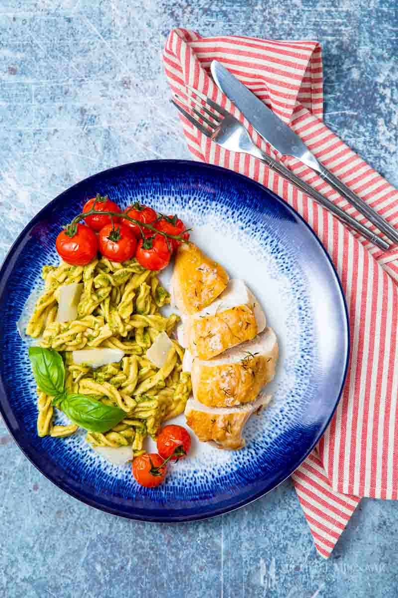 A plate of chicken pesto pasta, chicken breast, pasta with a green sauce
