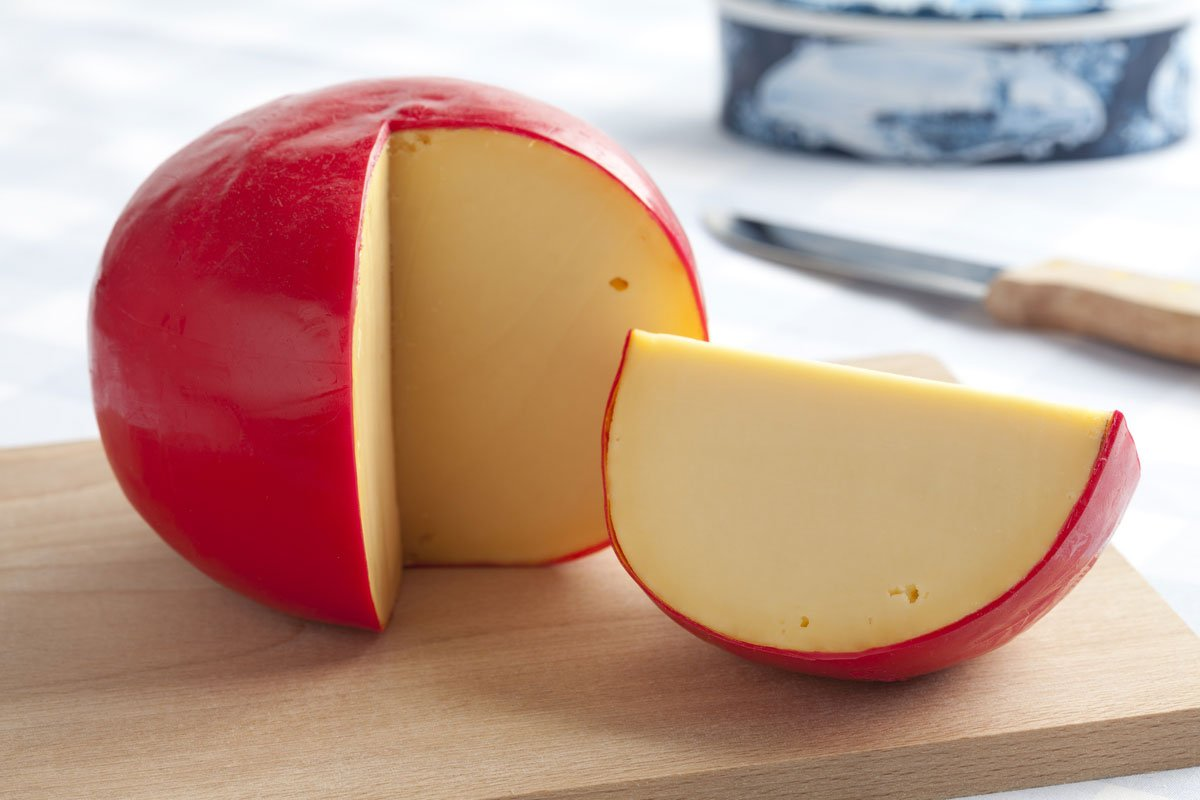 A round cheese block with a red rind