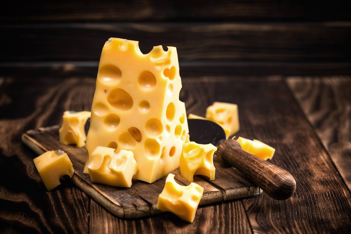 a tall triangle block of yellow emmental cheese with holes