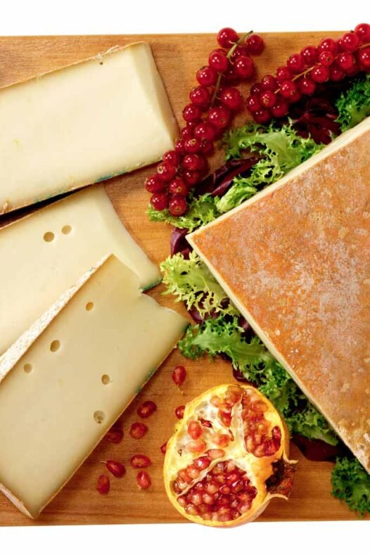 A block of white fontina cheese and fruit