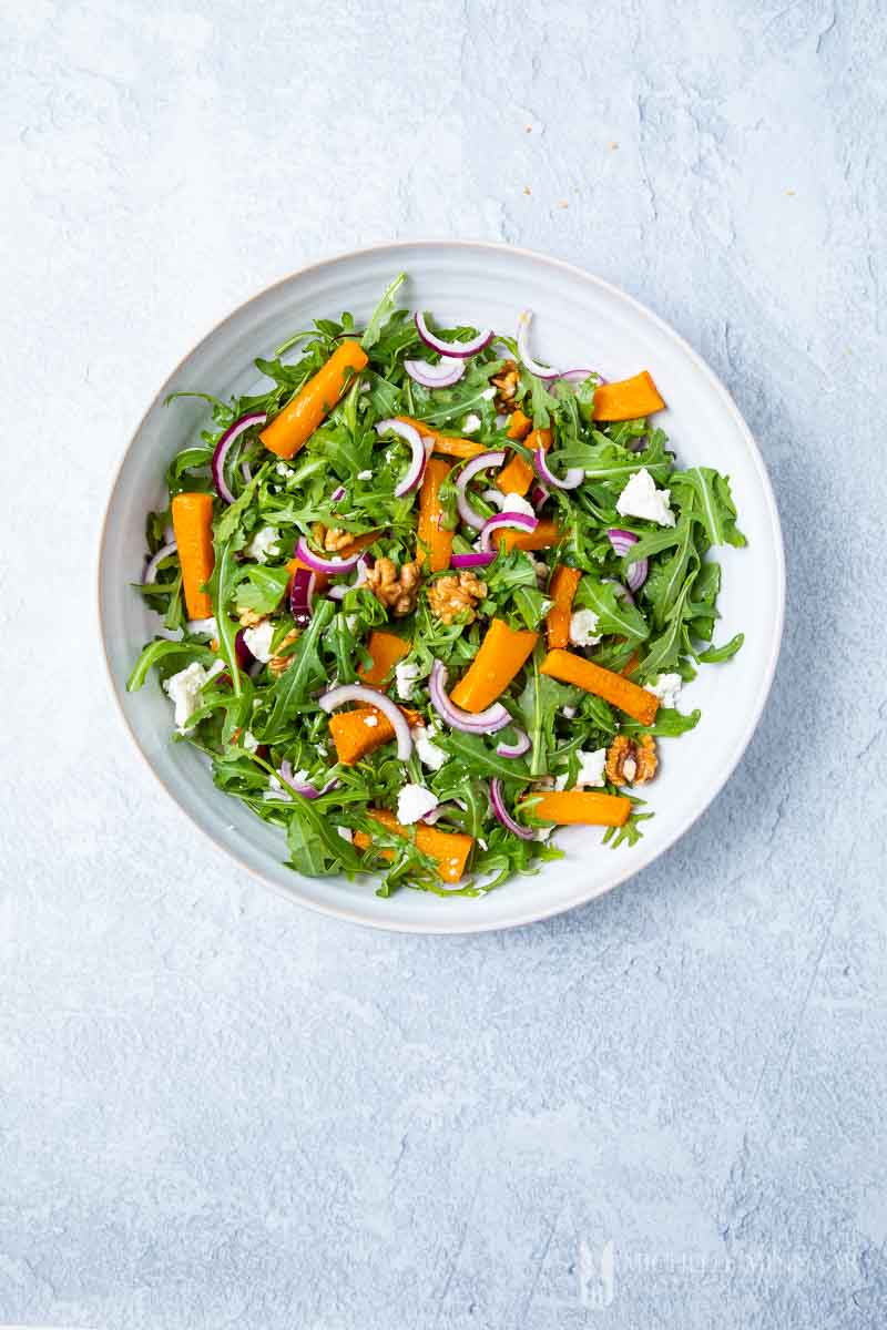 A round plate of pumpkin and feta salad