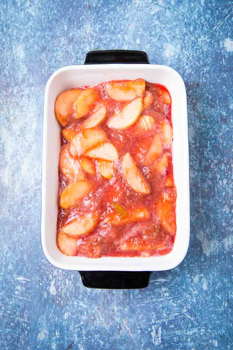 Apples in a white dish and red rhubarb sauce