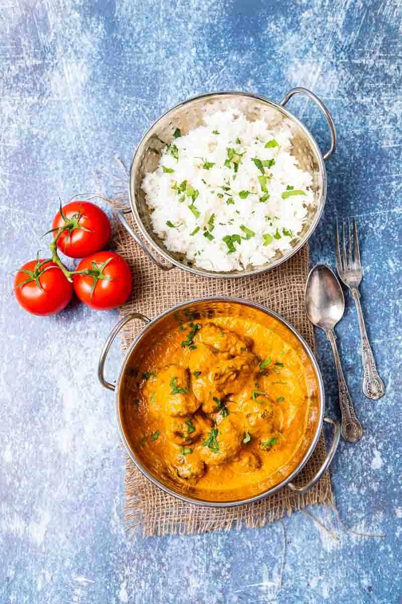 A bowl of lamb tikka masala and white rice