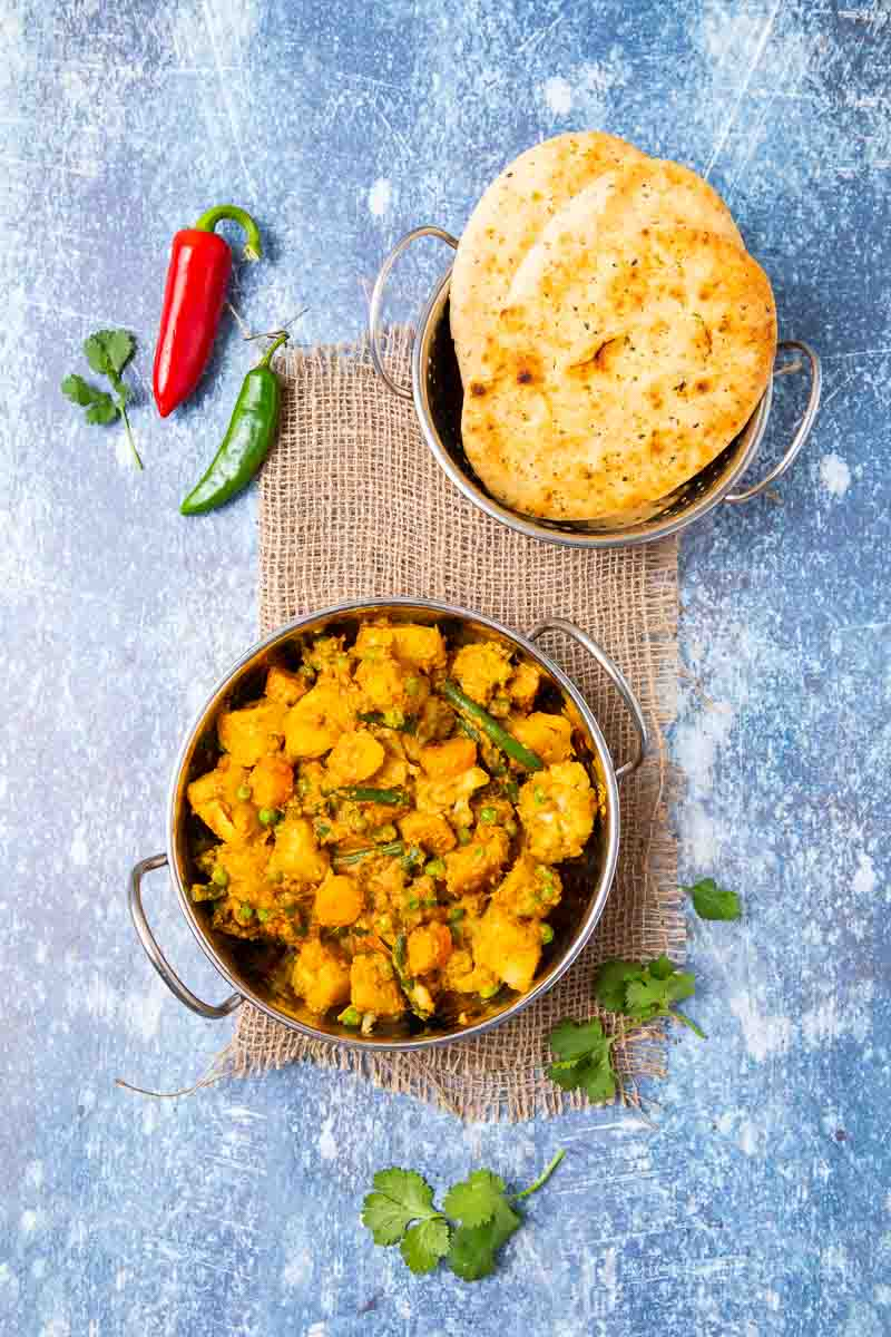 Freshly cooked mixed vegetable curry, naan and peppers