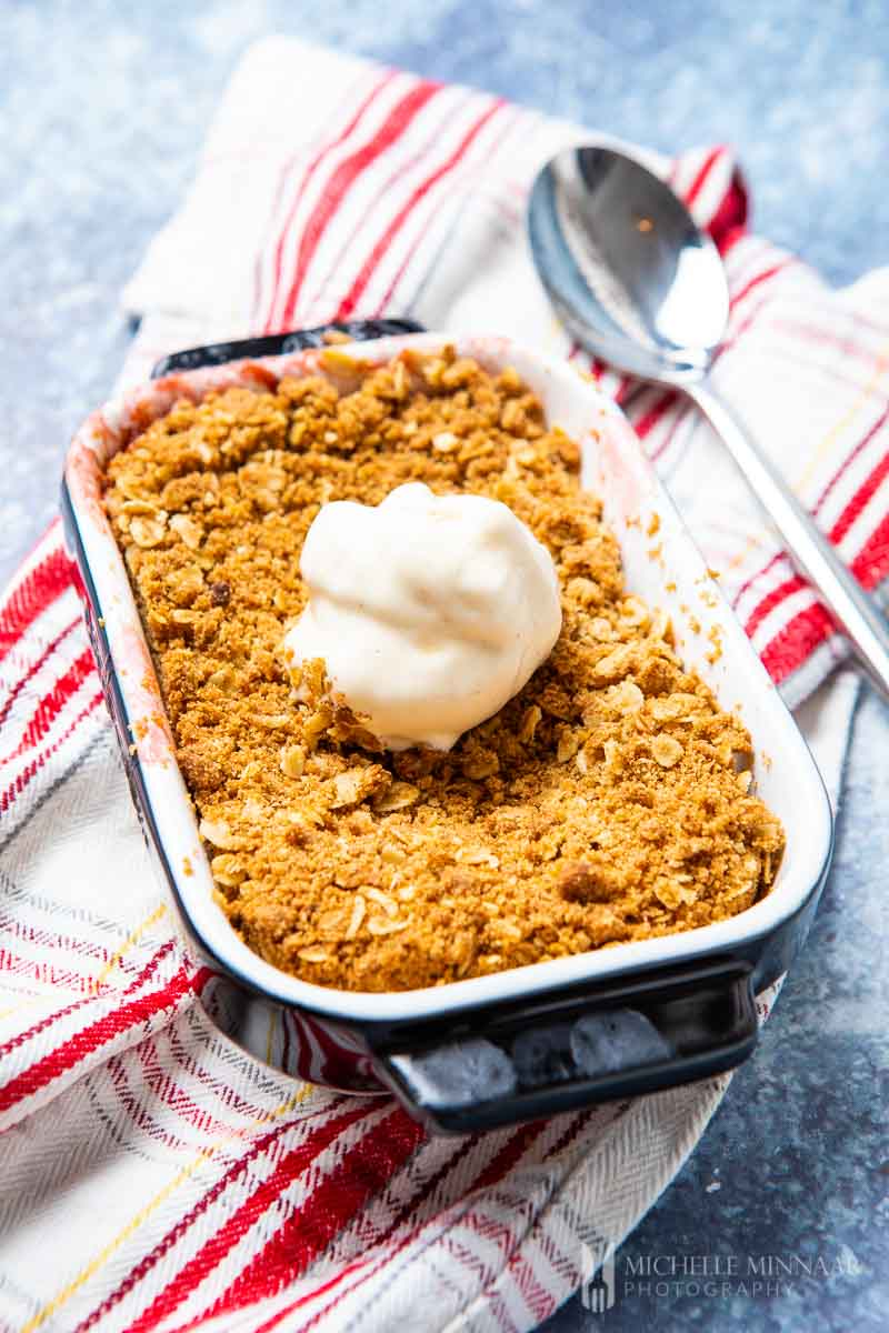 A apple and rhubarb crumble with a white scoop of ice cream