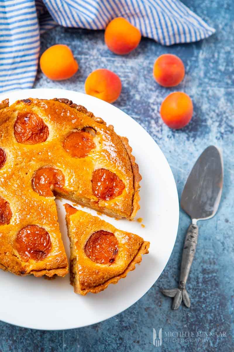A full apricot tart with a slice cut out