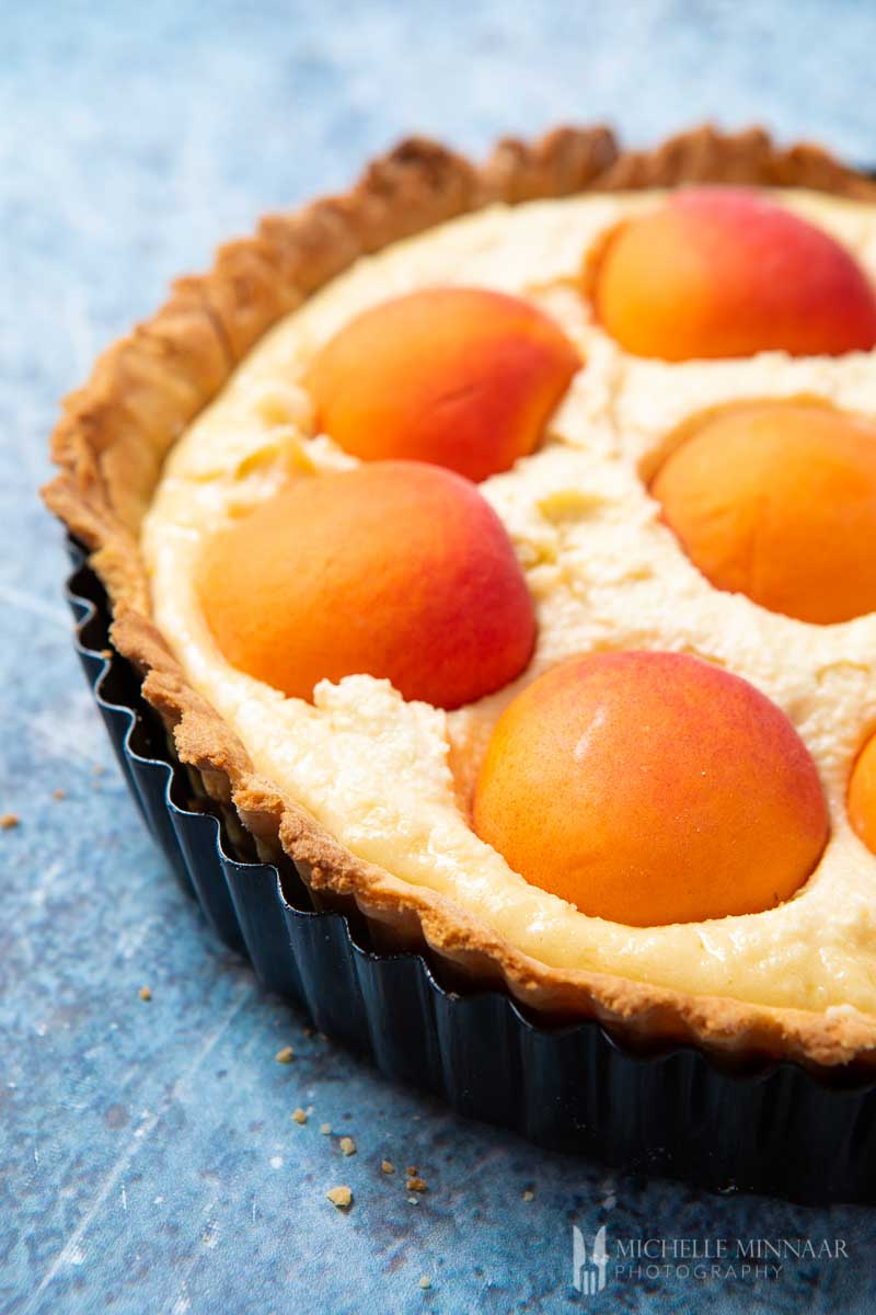 A close up of an apricot tart about to be baked