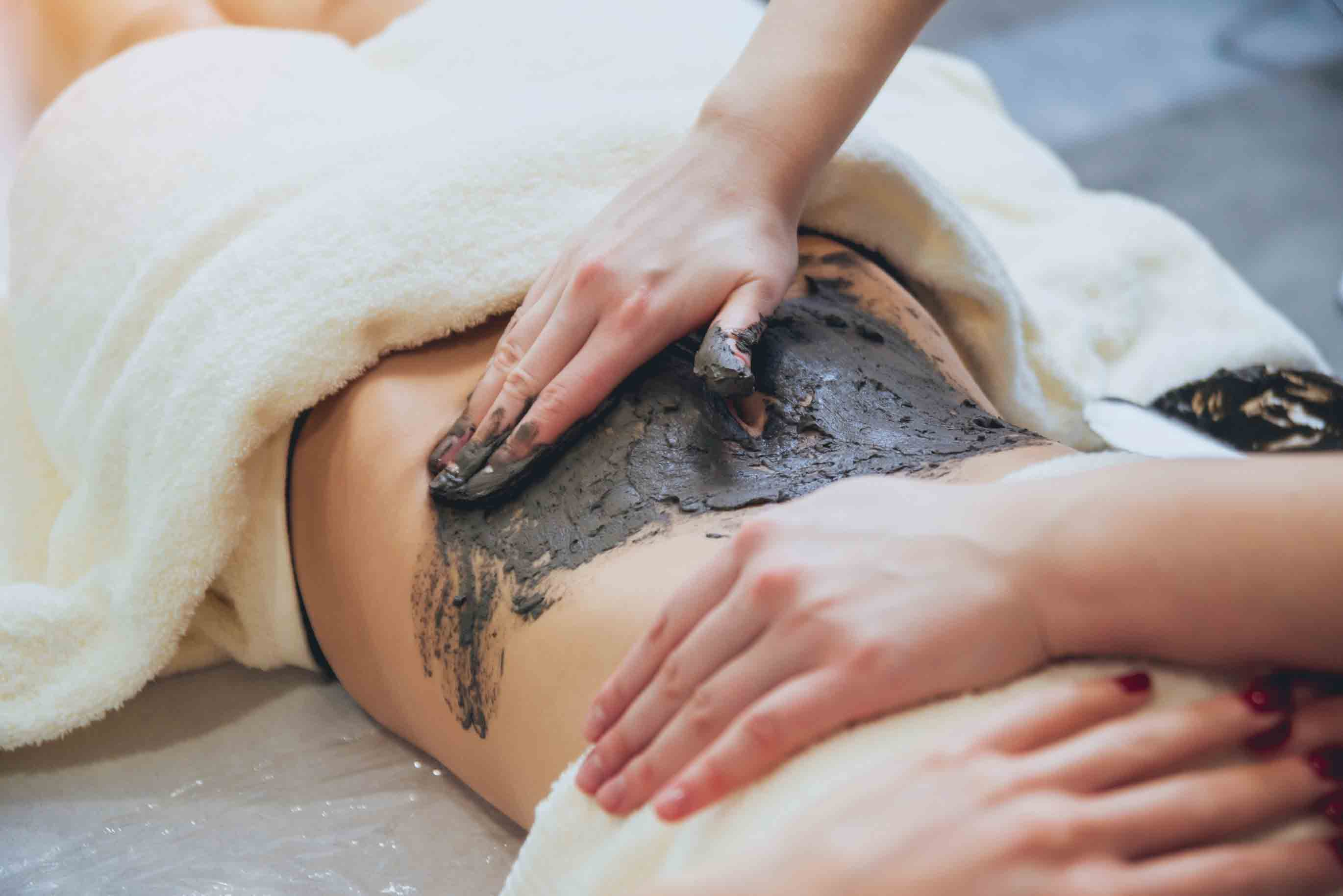 Seaweed body wrap being put on a womans back