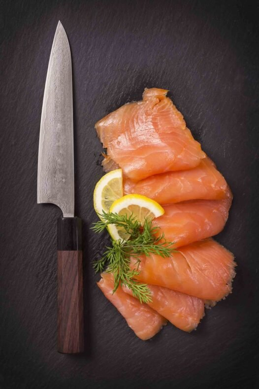 Sliced raw salmon and knife