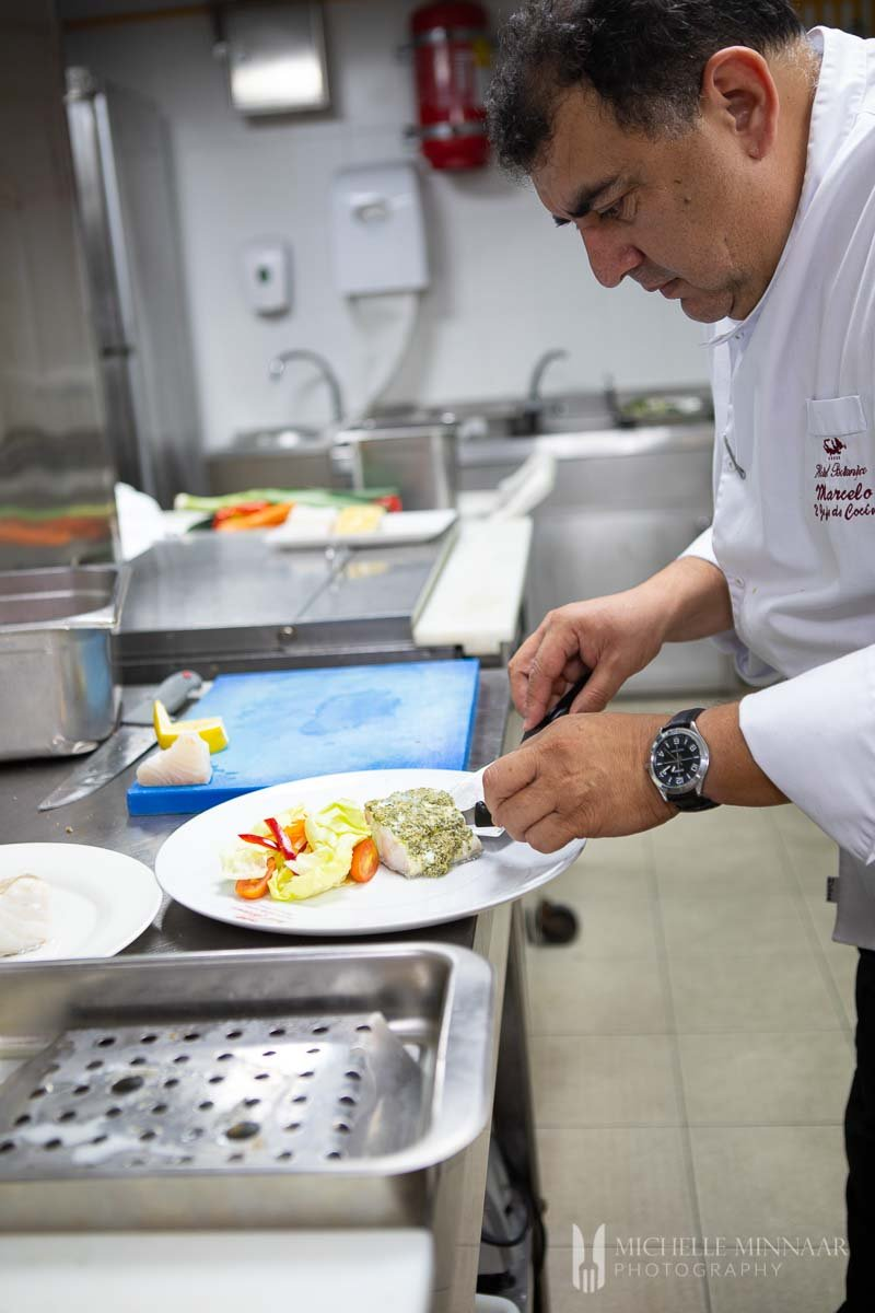 A chef plating steamed cod