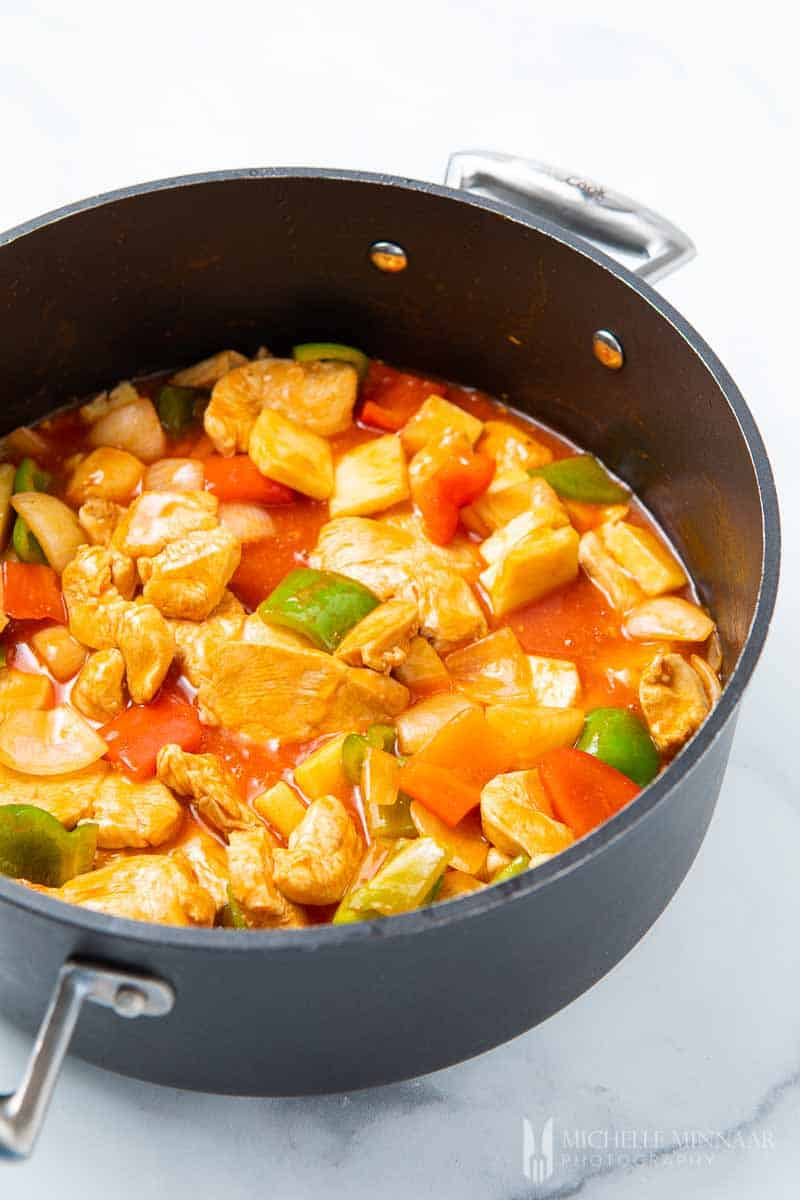 Chicken, peppers, pineapple simmering in a pot