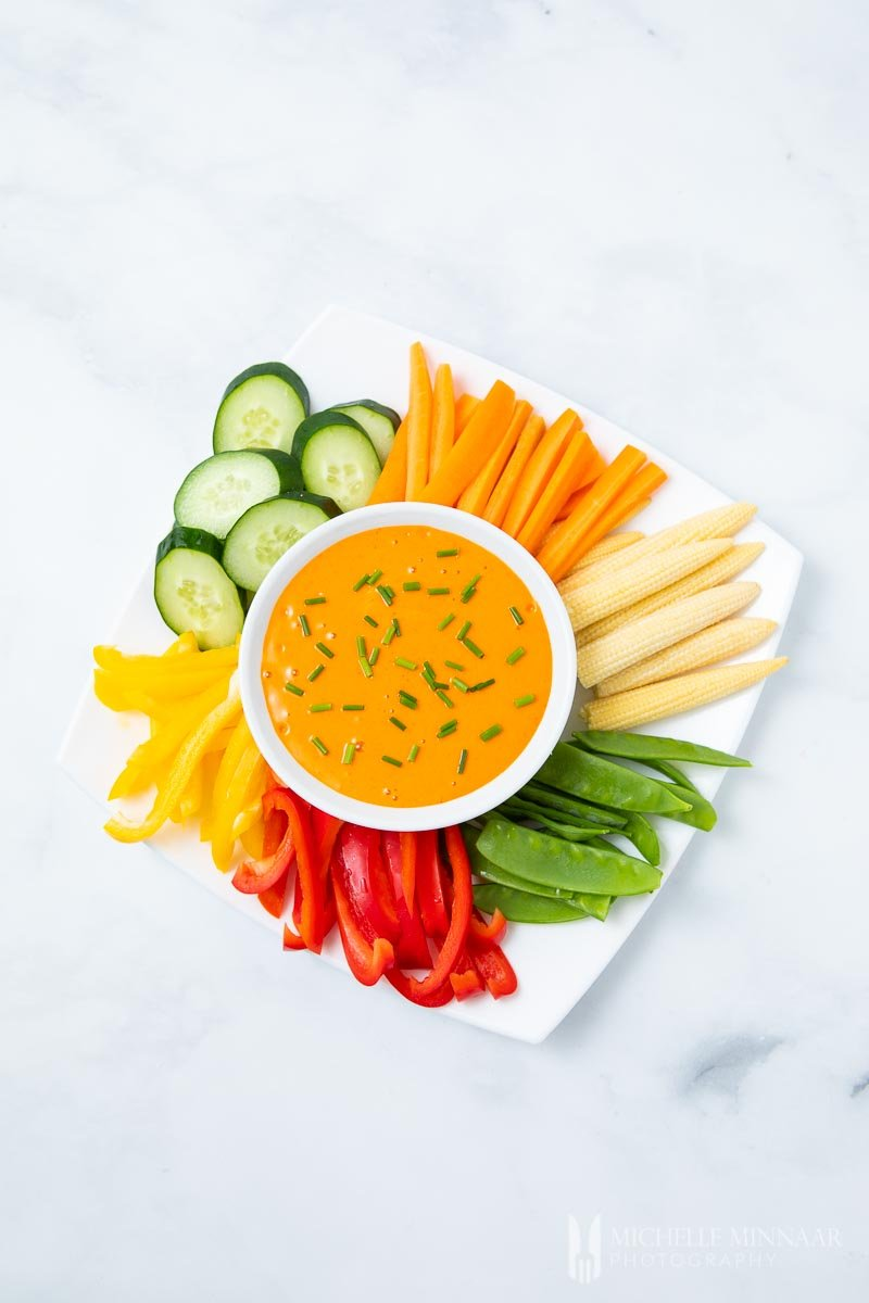 A bowl of orange harissa aioli with colorful cut vegetables