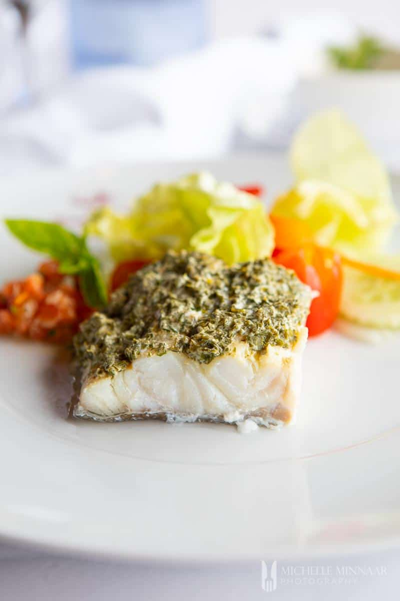A close up of steamed cod with a green sauce