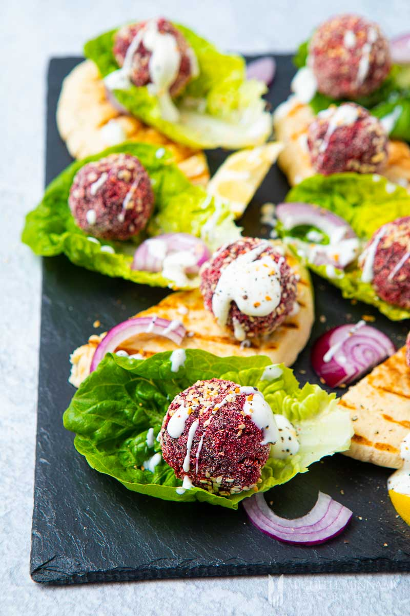Balls of purple beetroot in beds of lettuce