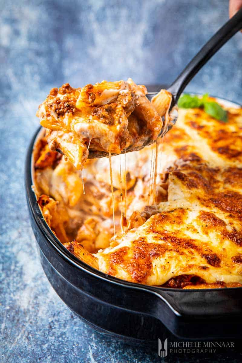 Slice of bolognese pasta bake on a spoon